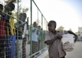 A young child carries a bucket full of cakes for sale at a football match in Mogadishu, Somalia, between the Somali Police Force and the Somali National Army on January 31. AU UN IST PHOTO / Tobin Jones
