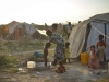 a-mother-gives-one-of-her-children-a-bath-outside-of-their-temporary-shelter-in-an-idp-camp-near-the-town-of-jowhar-somalia