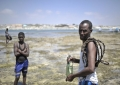 A Somali man carries a bottle and rope he found on a sand bank off of Lido beach in Mogadishu, Somalia, on January 31. The Mogadishu lifeguards, consisting entirely of a volunteer force of fisherman, began patrolling Lido beach in September 2013 after a spate of drownings. Mogadishu's beaches have become a popular destination for the city's residents since al Shabab withdrew the majority of its militants from the city in 2011. AU UN IST PHOTO / Tobin Jones