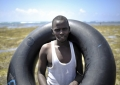 A young man poses with an old inner tube on a sand bank off of Lido beach in the Somali capital of Mogadishu on January 31. The Mogadishu lifeguards, consisting entirely of a volunteer force of fisherman, began patrolling Lido beach in September 2013 after a spate of drownings. Mogadishu's beaches have become a popular destination for the city's residents since al Shabab withdrew the majority of its militants from the city in 2011. AU UN IST PHOTO / Tobin Jones