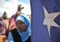 A young woman holds the Somali flag during a demonstration by a local militia, formed to provide security in Marka, Somalia, on April 30. AU UN IST PHOTO / Tobin Jone