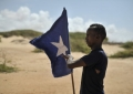 A young man carries the Somali flag while leading a group of soldiers during a demonstration by a local militia, formed in order to provide security in the town of Marka, Somalia, on April 30. AU UN IST PHOTO / Tobin Jones